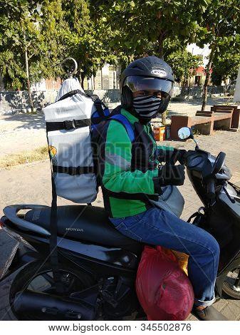 Semarang, Central Java, Indonesia - June 11, 2019: Grab Motorbike Driver Waiting For Customer On Ba
