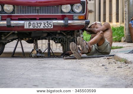 Havana, Cuba - May 17, 2019: Dirty Cuban Car Mechanic Is Working Underneath The Vehicle In The Stree