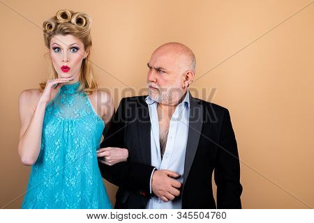 Difference Of Ages Concept. Couple Of Younger Woman And Elder Man Isolated At Orange Background. Cra