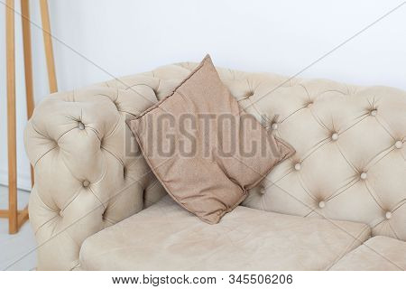 Textured Interior Sofas And Neutral Tones. Pillow On The Sofa In The Room. Brown Pillow On A Stylish