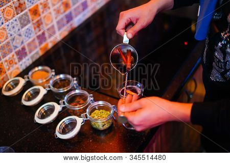 Mulled Wine Preparation, A Teapot In Hands, Pours Mulled Wine Into A Transparent Glass, Next To It T