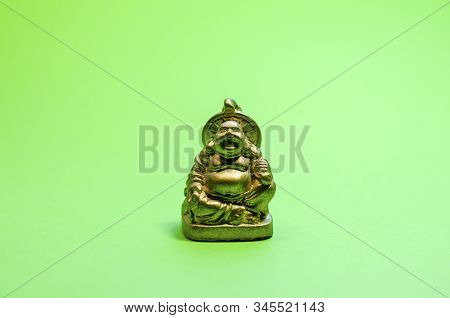 Statuette Of A Golden Hotei On A Green Background With Copy Space. Feng Shui