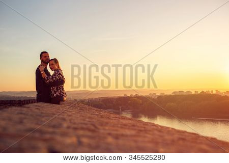 Enjoying Time Together. Young Man And Woman Hugging At Sunset