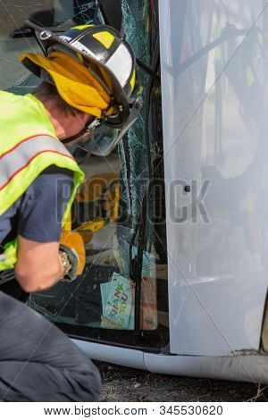 Vertical Shot Of Mergency Responder Sawing Through A Mini Van Window At Accident Site