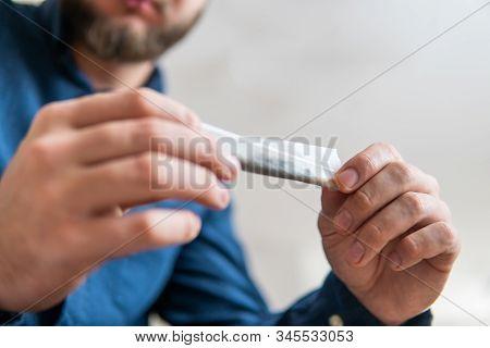 Close Up Of Addict Lighting Up Marijuana Joint With Lighter. Man Rolling A Marijuana Joint. Man Prep