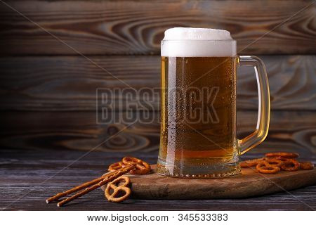 A Large Mug Of Cold, Fresh, Tasty, Lager Beer With Foam And A Snack Of Salted Pretzels And  Sticks.