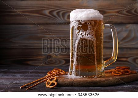 A Large Mug Of Cold, Fresh, Tasty, Lager Beer, With Foam Flowing Down And Snacks From Salted Pretzel
