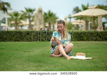 Young Beautiful European Blondie Girl Sitting On Green Lawn Of Hotel And Texting In Mobile Phone. Sh