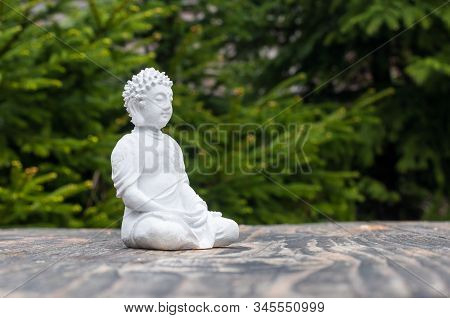 Statue Of Buddha - Peaceful Mind. White Deity On Blur Green Background. Meditate Concept