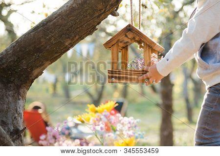 Bird Feeder On A Tree. The Child Feeds The Birds, Handmade Feeder. Wooden Feeders For Birds And Squa