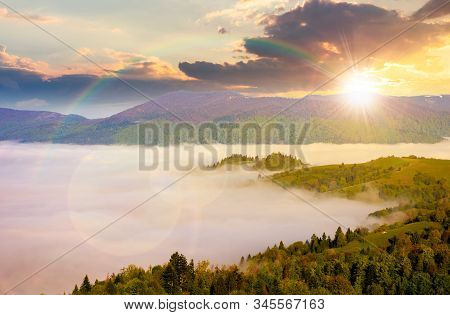 Mountainous Countryside At Sunset. Valley Full Of Rising Fog In Evening Light. Green Foliage On Tree
