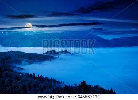 Mountainous Countryside At Night. Valley Full Of Rising Fog In Full Moon Light. Green Foliage On Tre