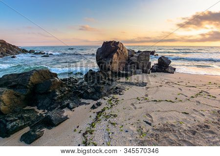 Sea Beach At Sunrise. Calm Waves Wash Huge Rocks. Golden Clouds On The Sky. Stunning Marine Scenery