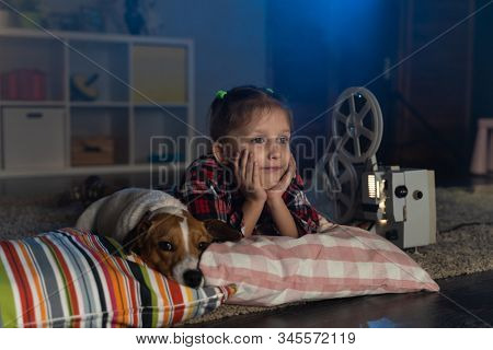 Girl child watching an old movie on a retro vintage film projector with a dog Jack Russell Terrier at home