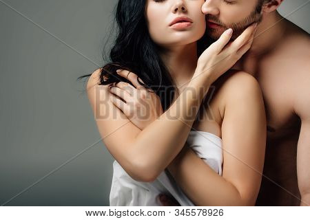 Sensual Naked Couple Hugging In Sheets, Isolated On Grey