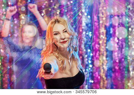 Portrait Of Happy Pretty Blonde Having Fun And Singing At Karaoke Club