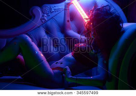 Sexy Young Woman In Erotic Fetish Wear Dancing Striptease In Nightclub. Beautiful Nude Body Of Sensu
