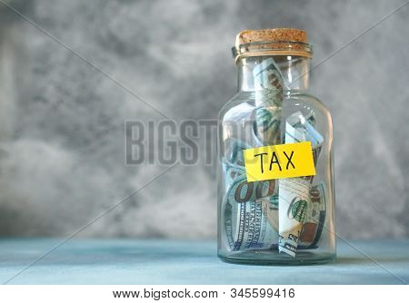 Taxes. Money For Tax Concept With Glass Jar Labeled Tax Filled With Money.
