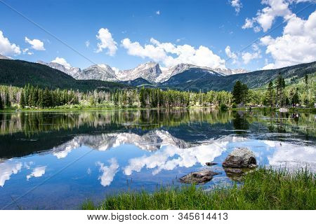 Beautiful Reflection Of The Rocky Mountains In The Sprague Lake With Green Pine Forest In The Backgr
