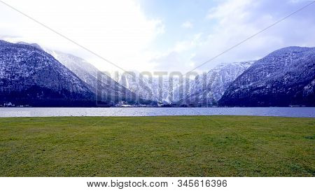 Panorama Of Hallstatt Lake And Green Grass Field Outdoor Dreamscape With Snow Mountain Background In
