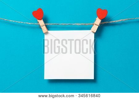 Square Sheet Of Paper On Rope. Clothes Pegs With Red Wooden Hearts. Valentines Day Background, Copy