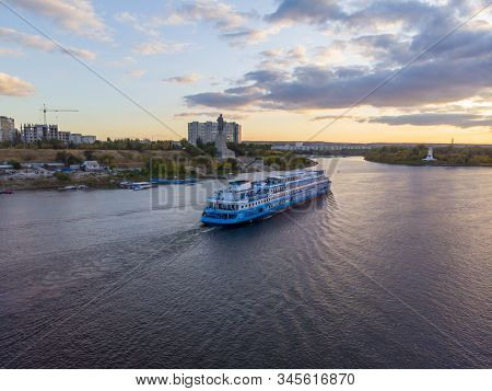 Travels. A Large Blue-white Cruise Ship With Tourists On Board Runs Downstream The Volga And Enters