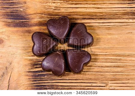 Heap Of Heart Shaped Chocolate Candies On Wooden Table. Top View. Valentine Day Concept