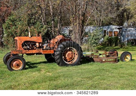 Downer, Minnesota, October 6, 2019: The Tractor Pulling A Hay Mower Is An Allis Chalmers, A U.s. Man