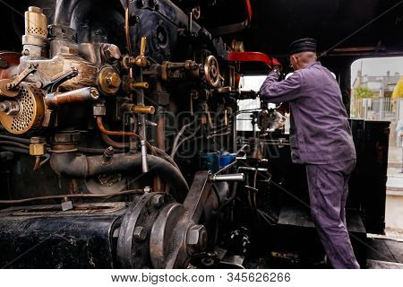Selective Focus On Steam Engine Elements Or Parts In Steam Train Cabin With Unrecognisable Engineer