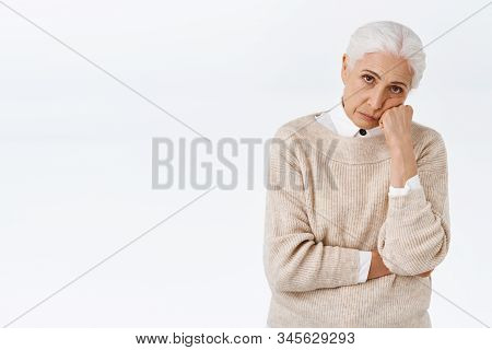 Bored Or Annoyed Senior Lady With Grey Combed Hair, Lean Face On Fist, Look From Under Forehead Dist
