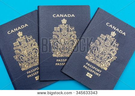 Three Canadian Passports Spread Out On Bright Blue Flat Lay Background. Travel And Vacation Concept.
