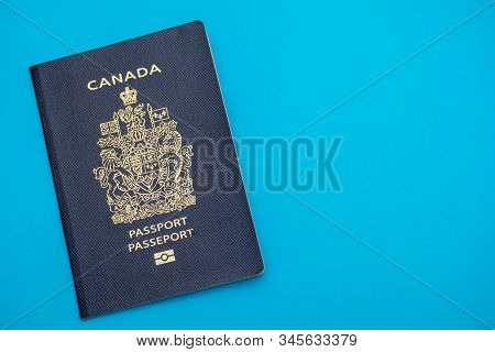 Canada Passport On Bright Blue Flat Lay Background. Travel And Vacation Concept.