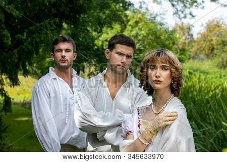 A Romantic Love Triangle Between Two Men And A Woman Dressed In Period Clothing Standing On River Em