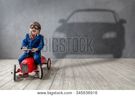Happy Child Wants To Race. Funny Kid Dreams About A Car. Imagination, Freedom And Motivation Concept