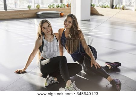 Cheerful Attractive Caucasian Women, Two Sportswoman In Sportswear, Sitting Gym Floor, Fitness Club,