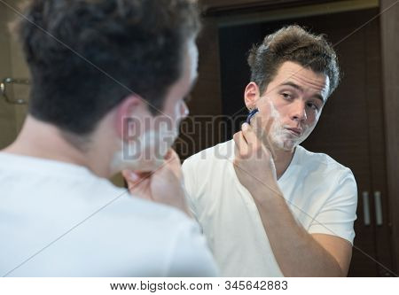 young caucasian man shaving face with razor looking at mirror reflection in bathroom morning clean