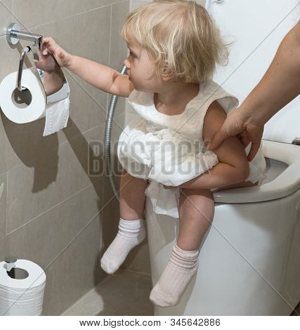 little child baby sitting on toilet holding toilet paper