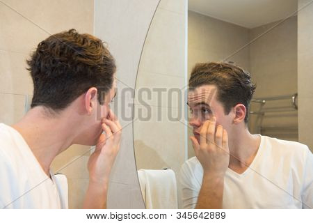 young caucasian man taking care of his face  looking at mirror reflection in bathroom morning clean eyes