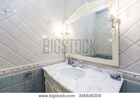 White Bathroom In A Classic Style. Sink, Mirror In A Carved Frame, Water Tap And Lamps In The Bathro