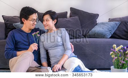 Couple And Love Concept - Young Asian Couple Hugging In Love At Front Of Sofa In Home On Valentines
