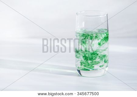 Chlorophyll In Glass Of Water On White Wooden Background. Copy Space, Sunlight.