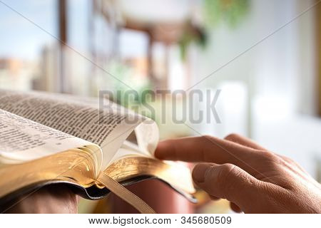 A Man Holds A Bible And Reads A Book On The Terrace. Morning Time.