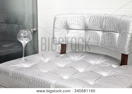 Large Modern Silver Chair And A Glass Of Water In The Room