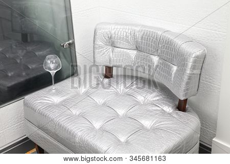 Silver Small Sofa And A Glass Of Water In The Room