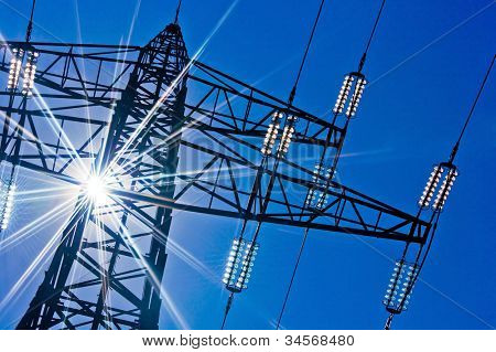 a high-voltage electricity pylons against blue sky and sun rays