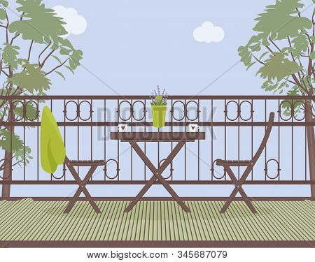 Wooden Garden Furniture On The Balcony With Wrought Iron Railings With A Green Pot With Lavender Flo