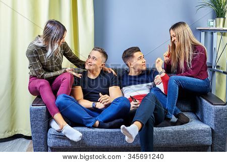 Students Chatting In One Of The College Dorm Rooms. Young Men And Women Play Intellectual Games In A