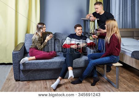 Friends Met At A Party In A Student Dormitory Or Apartment. Young People Talk, Laugh And Drink Wine,