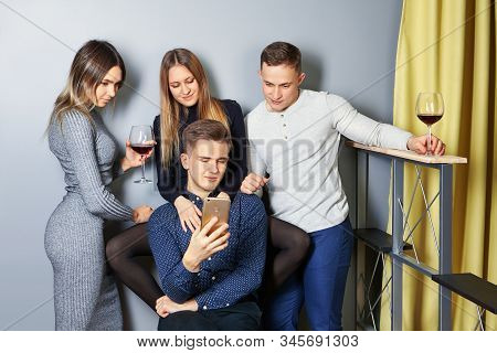 Young Men And Women Are Viewing Photos From A Student Party On Screen Of A Cell Phone Or Smartphone.