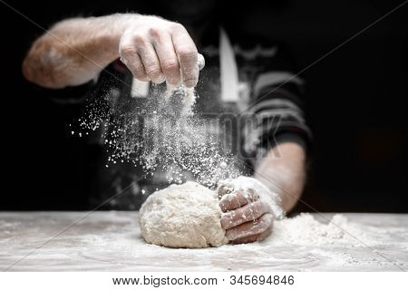 White Flour Flies In Air On Black Background, Pastry Chef Claps Hands And Prepares Yeast Dough For P